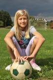 Flicka som sitter på ett fotbollfält Arkivfoto