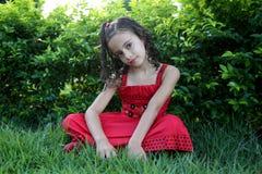 Flicka som sitter på gräset Arkivfoto