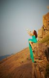 Flicka som sitter på kanten av en klippa. Royaltyfri Foto