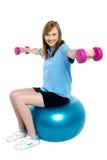 Flicka som sitter på pilatesboll och gör hantlar Arkivbild