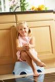 Flicka som sitter på Plastic moment i kök arkivbilder