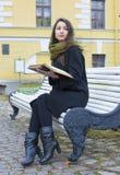 Flicka som sitter på en bänk och läser en bok Arkivbild