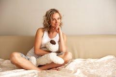 Flicka som sitter på soffan Royaltyfri Foto