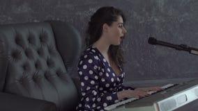 Flicka som sjunger in i mikrofonen och spelar tangentbordet stock video