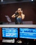 Flicka som sjunger i yrkesmässig studio med mic, hörlurar och datorer arkivbild