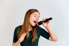 Flicka som sjunger med en mikrofon royaltyfri bild