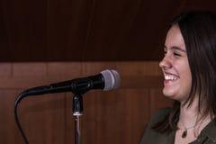Flicka som sjunger med en mikrofon i en musikstudio arkivbild
