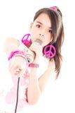 Flicka som sjunger med mikrofonen som pekar på dig arkivbild