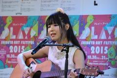 Flicka som sjunger och spelar en gitarr Royaltyfri Foto