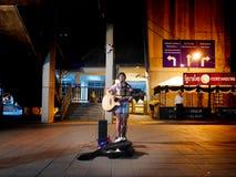Flicka som sjunger och spelar gitarren i Bangkok royaltyfria bilder