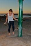 Flicka som sköljer strandsand av fot arkivbild