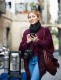 Flicka som söker för riktningen genom att använda hennes telefon i stad Royaltyfria Bilder