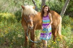 Flicka som skrattar med hennes gulliga isländska ponny Arkivbild