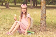 Flicka som skrattar och rymmer glass Royaltyfria Foton