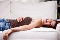 Flicka som skrattar på hennes soffa Arkivfoton
