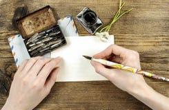 Flicka som skrivar ett brev med bläckpennan Arkivfoto