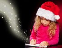 Flicka som skriver en bokstav till Santa Claus Arkivbild