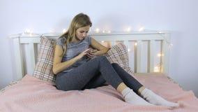 Flicka som skriver ett meddelande på telefonen arkivfilmer