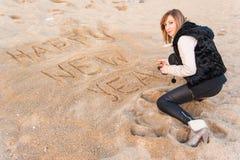 Flicka som skriver nytt år i sand arkivbilder