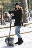 Flicka som skyfflar snö Royaltyfri Bild