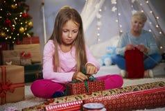 Flicka som slår in gåvor arkivfoton
