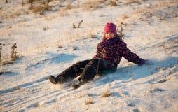 Flicka som sledding i ljuset av solnedgången Royaltyfria Foton