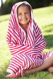 Flicka som slås in i handduken som sitter i trädgård Arkivbilder