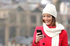 Flicka som smsar i en mobiltelefon i vinter Arkivbild
