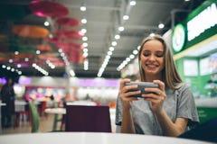 Flicka som smsar på den smarta telefonen i en restaurangterrass med en unfocused bakgrund Fotografering för Bildbyråer