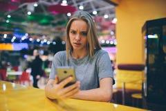 Flicka som smsar på den smarta telefonen i en restaurangterrass med en unfocused bakgrund Arkivbilder