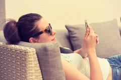Flicka som smsar på den smarta telefonen i en vardagsrum för hotellrestaurangterrass Royaltyfria Foton