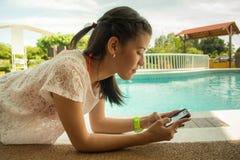 Flicka som smsar på pölsidan royaltyfria bilder