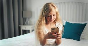 Flicka som smsar på smartphonen i sovrum stock video