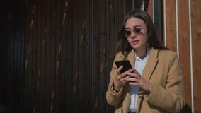 Flicka som smsar p? den utomhus- smartphonen arkivfilmer