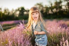 Flicka som sniffar blommor i ett lavendelfält Arkivfoton
