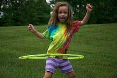 Flicka som snurrar ett Hula beslag Arkivfoto