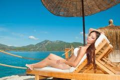 Flicka som solbadar i bungalowen som förbiser havet Royaltyfri Fotografi