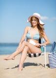 Flicka som solbadar på strandstolen Arkivfoto