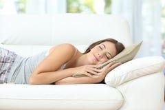 Flicka som sover eller ta sig en tupplur som är lycklig på en soffa arkivfoto