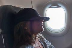 Flicka som sover i ett flygplan vid fönstret royaltyfria foton