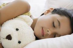 Flicka som sover i säng med Teddy Bear Arkivbilder