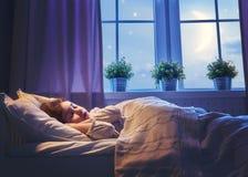 Flicka som sover i sängen royaltyfri bild