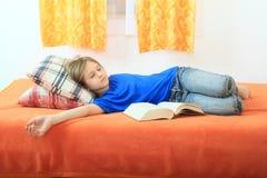 Flicka som sover med en bok Arkivfoton