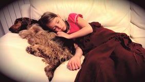 Flicka som sover med hennes älsklings- hund Arkivfoto