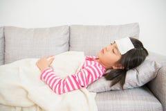 Flicka som sover och som är sjuk på soffan arkivfoto