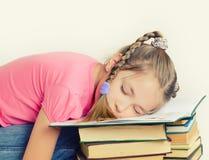 Flicka som sover på boken Royaltyfria Foton