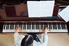Flicka som spelar bästa sikt för piano royaltyfri foto