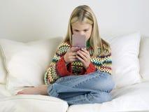 Flicka som spelar den Handheld videospelet på soffan arkivbild