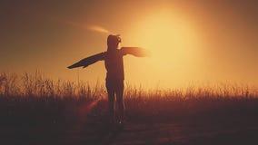 Flicka som spelar för att vara en klassisk pilot som bär en pälshatt, exponeringsglas och vingar som göras av papp som en leksak  stock video