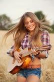 Flicka som spelar gitarren i ett vetefält Arkivbilder